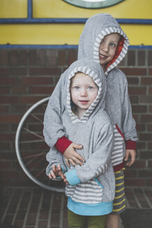 Portrait of two siblings wearing similar hooded jackets - IHF00058