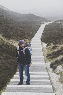 Man carrying his toddler son in baby carrier on his back, Sylt, Germany - IHF00064
