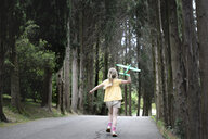 Girl with toy plane running on a treelined road - EYAF00250