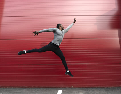 Athlete jumping in front of a red wall - AHSF00410