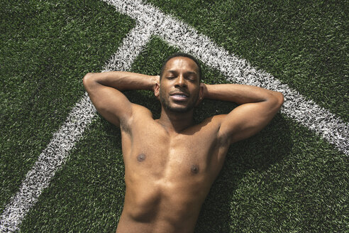 Athlete relaxing after workout on a lawn - AHSF00437