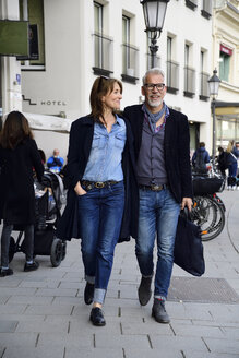 Mature couple walking in the city, with arms around - ECPF00761