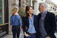 Mature couple walking in the city, man looking after an other woman - ECPF00767