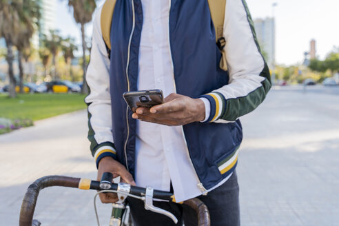 Close-up of casual businessman with bicycle using cell phone in the city, Barcelona, Spain - AFVF03036