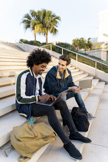 Two casual businessmen sitting on stairs working on laptop - AFVF03117