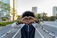 Portrait of casual man in the city making a heart with his hands, Barcelona, Spain - AFVF03159