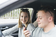Portrait of young woman in a car watching her boyfriend on driver's seat using smartphone - FBAF00640