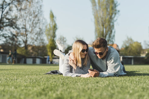 Young couple wearing sunglasses lying on a meadow looking at cell phone - FBAF00658