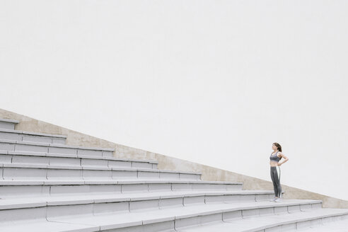 Sportswoman standing and looking up on concrete bleachers - AHSF00477