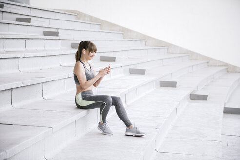 Young woman in sportswear sitting on concrete bleachers and listening music on a smartphone - AHSF00489