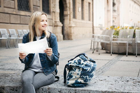 Smiling blond woman with map and baggage sitting on curb looking around - HMEF00427