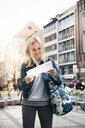 Portrait of smiling blond woman baggage looking at map in the city, Munich, Germany - HMEF00430