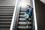 Woman with backpack and travelling bag standing on escalator looking up - HMEF00436