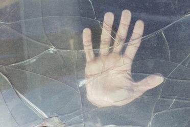 Hand of a young man behind broken windscreen on a scrapyard - JPTF00076