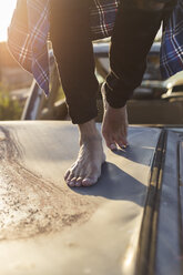 Young man walking barefoot on car roof on a scrapyard - JPTF00082