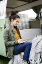 Young woman sitting in her camper, writing in a notebook - HMEF00438