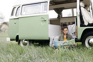 Young woman studying map, sitting in the grass, in front of her camper - HMEF00444