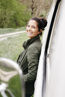 Laughing young woman leaning on camper - HMEF00450