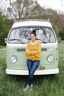 Young woman staniding in front of her camper with arms crossed - HMEF00462