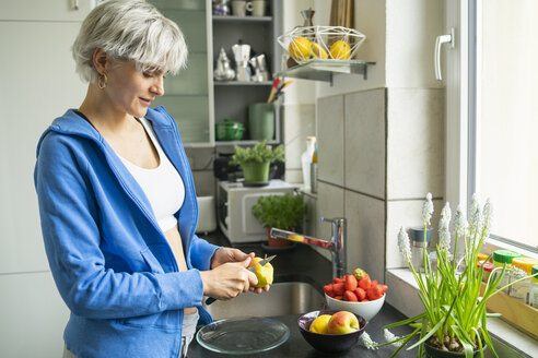 Woman chopping fruits in her kitchen - FBAF00671