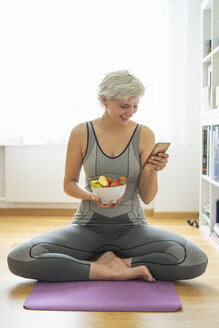 Woman practising yoga at home, having a healthy fruit snack, using smartphone - FBAF00683