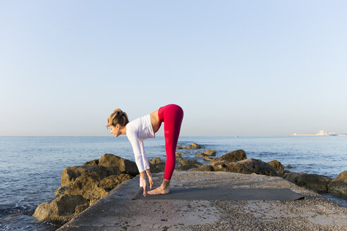 Young woman practicing yoga on the beach, doing sun salutations - JPTF00091
