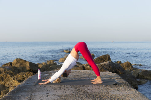 Young woman practicing yoga on the beach, doing downward facing dog - JPTF00094
