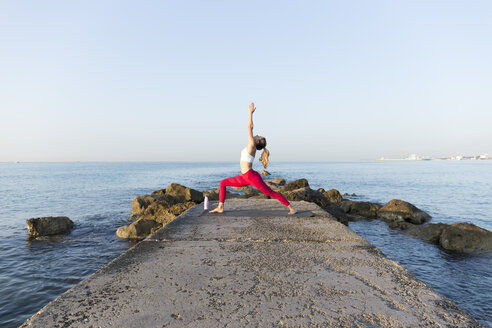 Young woman practicing yoga on the beach, doing warrior pose - JPTF00097