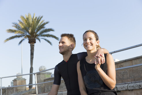 Sporty young couple relaxing on the coast after exercise - JPTF00109
