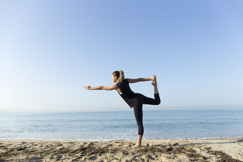 Young woman practicing yoga on the beach, doing dancer pose - JPTF00121