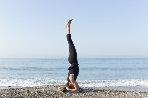Young woman practicing yoga on the beach, doing headstand - JPTF00124