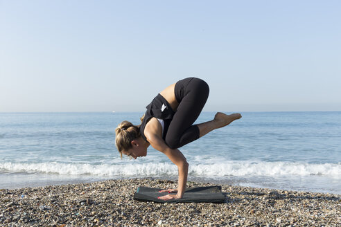 Young woman practicing yoga on the beach, doing crane pose, kakasana - JPTF00127