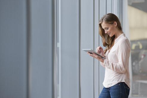 Woman using digital tablet near window - JUIF01056