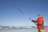 Senior man fishing on sunny beach - JUIF01119