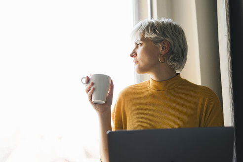 Woman looking out of window at home with laptop and coffee cup - FBAF00698