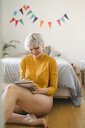 Smiling woman sitting next to bed at home taking notes - FBAF00701