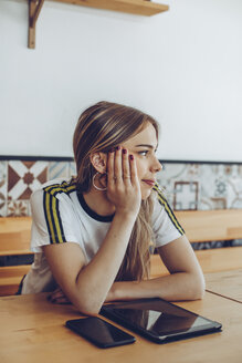 Young woman sitting in a cafe looking away - ACPF00519