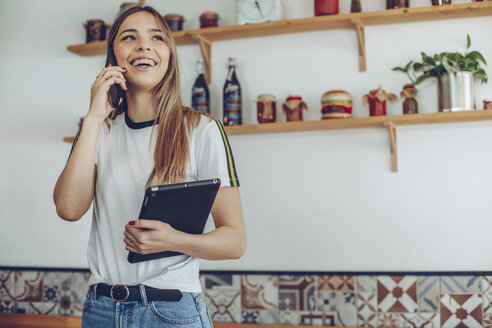 Portrait of young woman talking on the phone in a cafe - ACPF00522