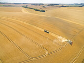 Aerial landscape view of combine harvester and tractor trailer in sunny golden barley field - JUIF01154