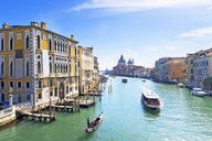 Gondolas and boats in sunny Grand Canal in front of Santa Maria della Salute and architectural buildings in Venice, Italy - JUIF01169