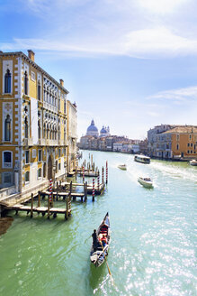 Gondolas and boats in sunny Grand Canal in front of Santa Maria della Salute and architectural buildings in Venice, Italy - JUIF01172