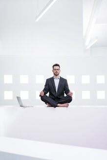 Businessman doing yoga in office next to laptop - MOEF02201