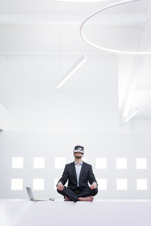 Businessman wearing VR glasses in office next to laptop - MOEF02204