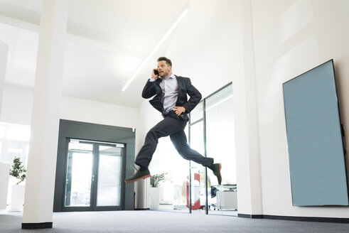 Businessman on cell phone jumping in office - MOEF02213