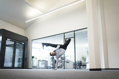 Businessman with cell phone doing a one-handed handstand on office floor - MOEF02216