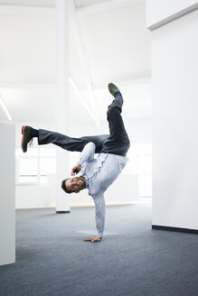 Businessman with cell phone doing a one-handed handstand on office floor - MOEF02219