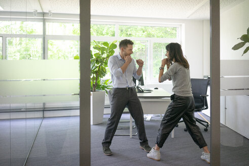 Businessman and businesswoman fighting in office - MOEF02222