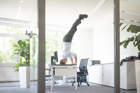 Businessman doing a headstand on desk in office - MOEF02231