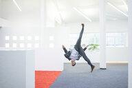 Businessman jumping mid-air on office floor - MOEF02237