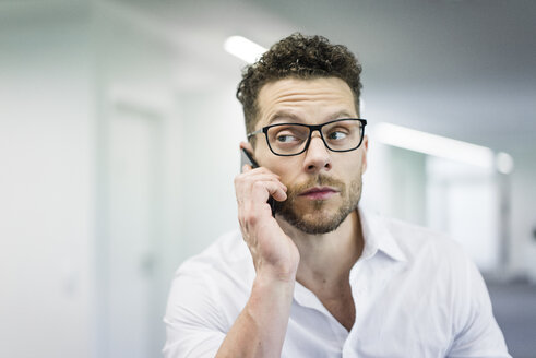 Portrait of businessman on cell phone in office - MOEF02249